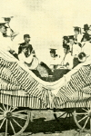 Photographic Postcard of  A Women's Brass Band on a Horse-Drawn Parade Float Wagon (1909)