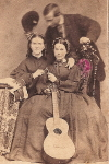 Carte de Visite of  two women with guitar (possibly English) holding wishbone with man bowing behind,  c. 1860